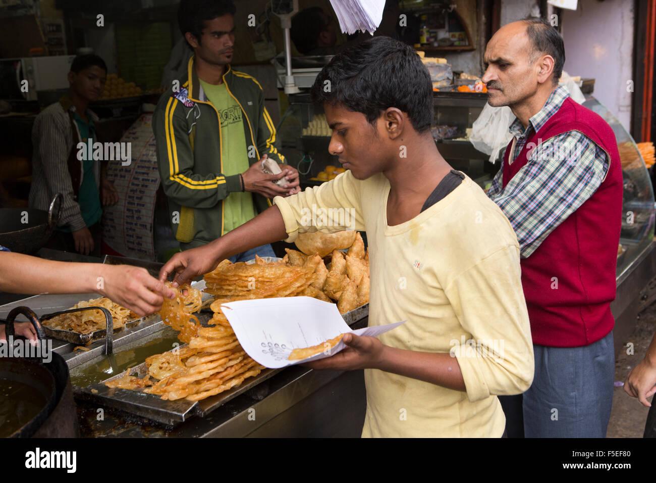 India, Himachal Pradesh, Shimla (Simla), Lower Bazaar, sweet stall, man selecting jelabi from display - Stock Image