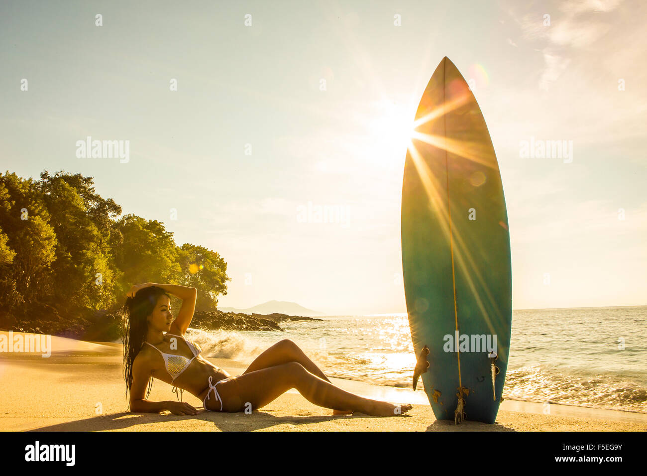 Woman lying on the beach with a surfboard, Bali, Indonesia - Stock Image