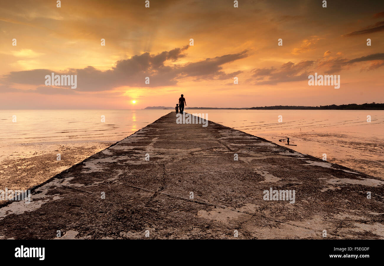 Silhouette of a man and his son standing at the end of a jetty, Port Dickson, Malaysia - Stock Image