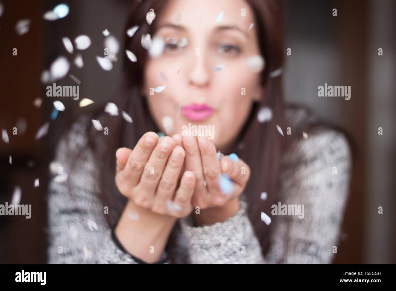Woman blowing confetti in her hands - Stock Image