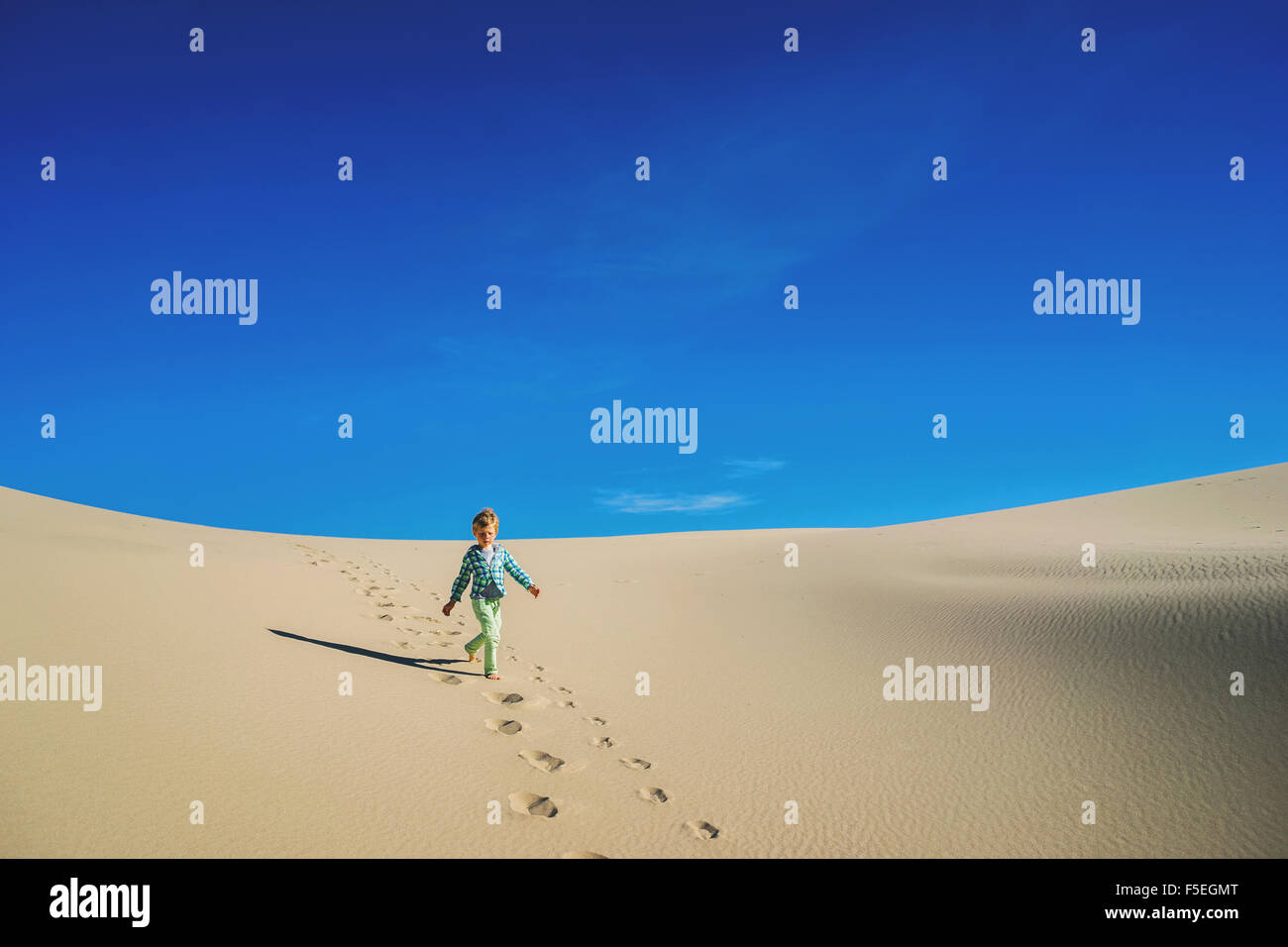 Boy running down a sand dune - Stock Image