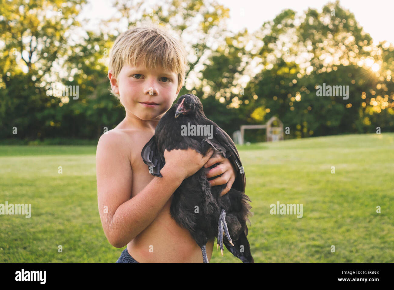 Portrait of a Boy holding q chicken - Stock Image