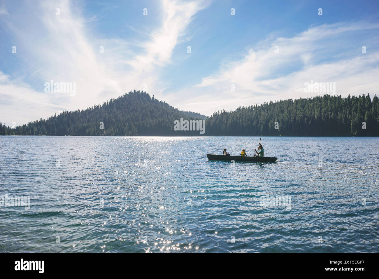 Man with two sons in a rowing boat - Stock Image