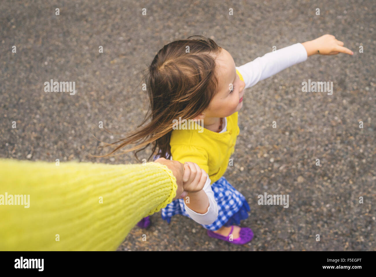Overhead view of a girl holding her mother's hand - Stock Image