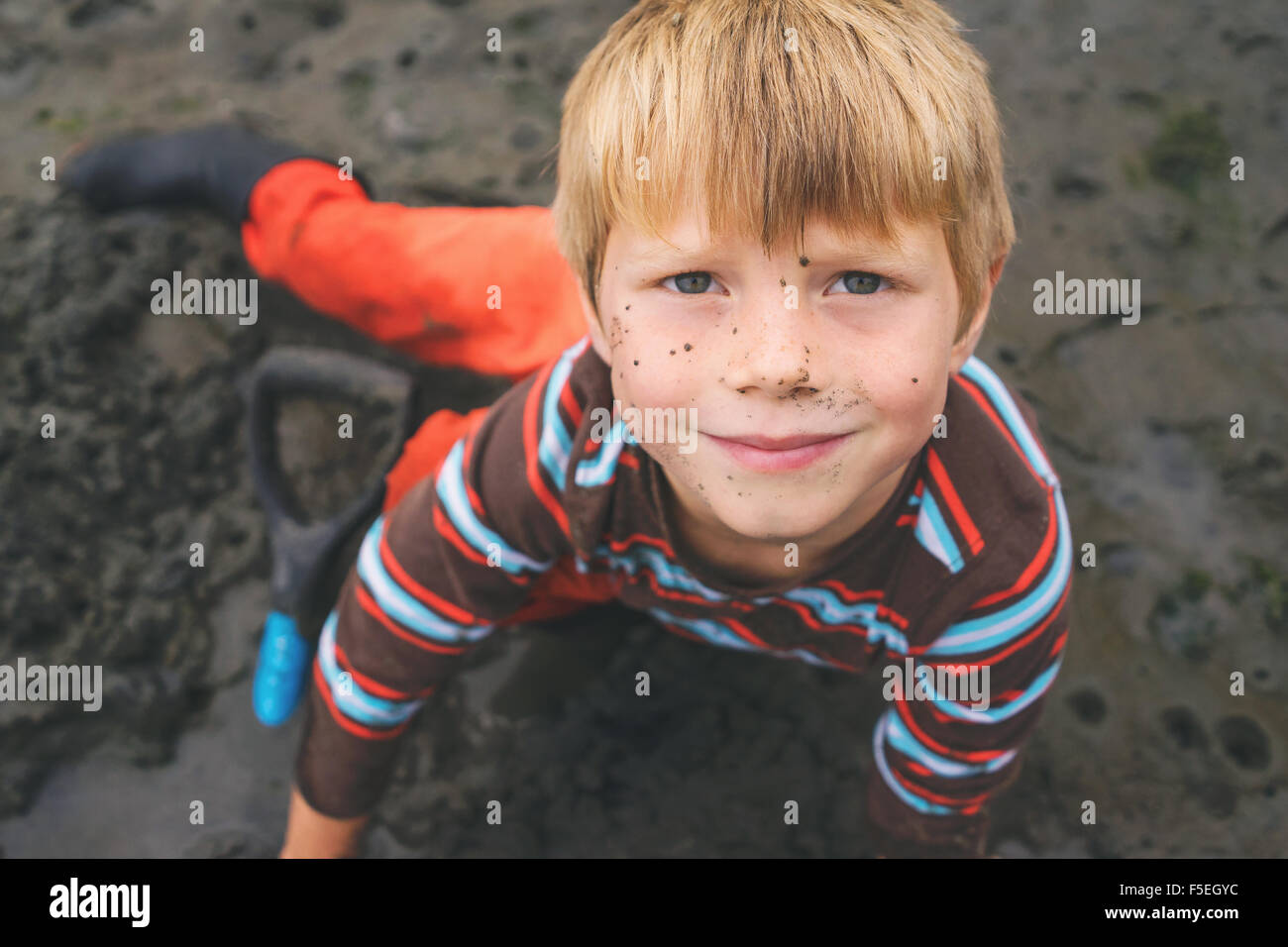 Portrait of a boy digging for clams in wet sand - Stock Image