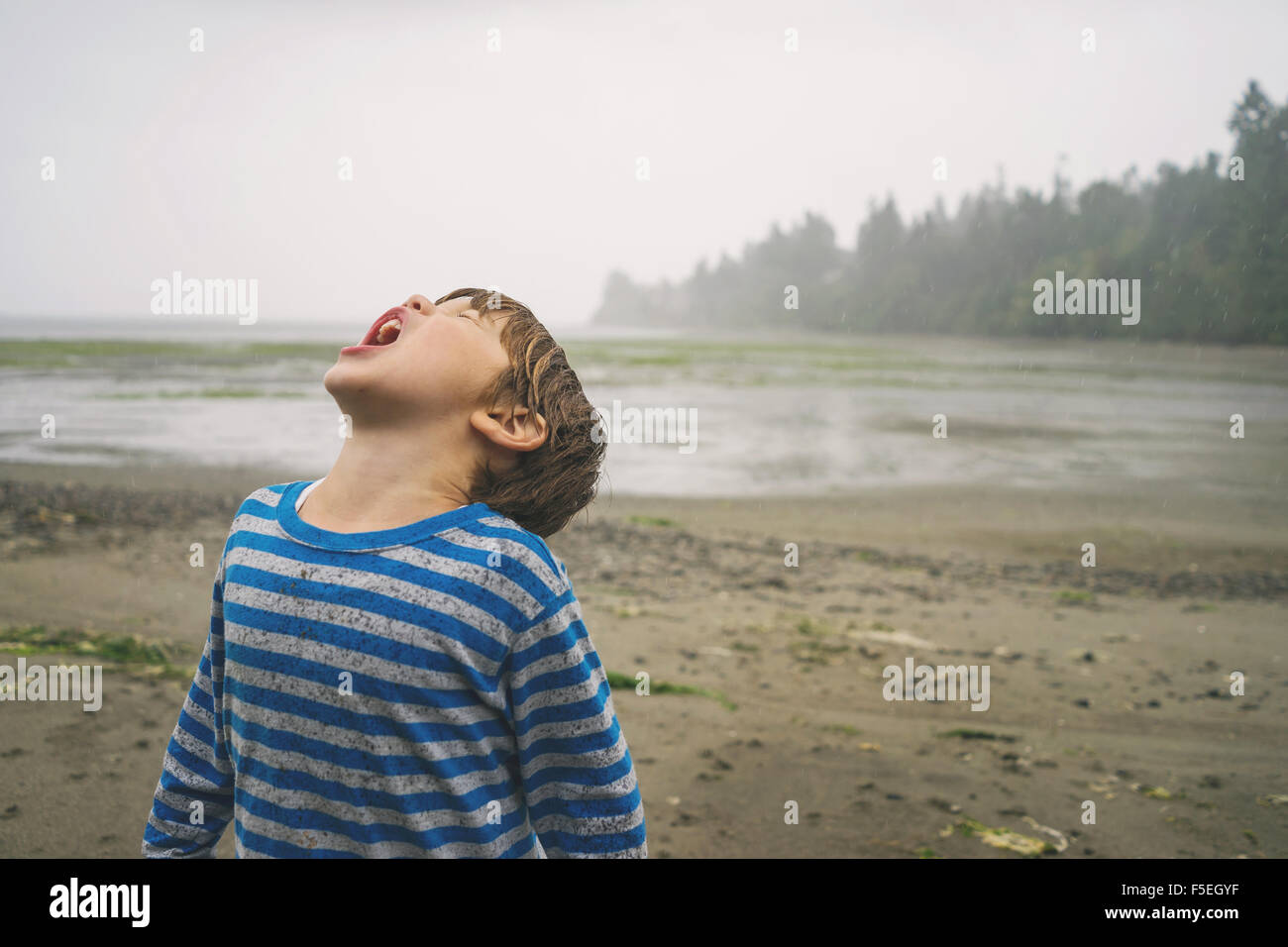 Boy with his head tilted back catching rain in mouth - Stock Image