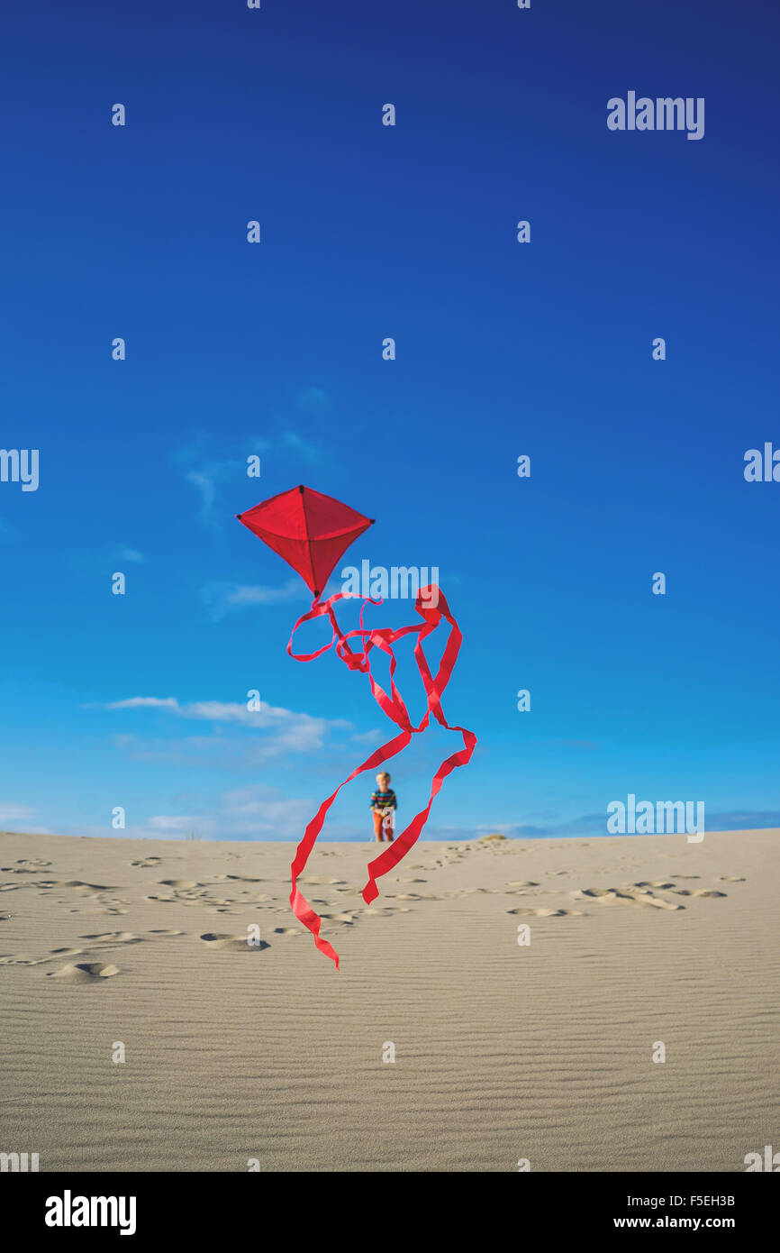 Boy flying red kite on sandy beach - Stock Image