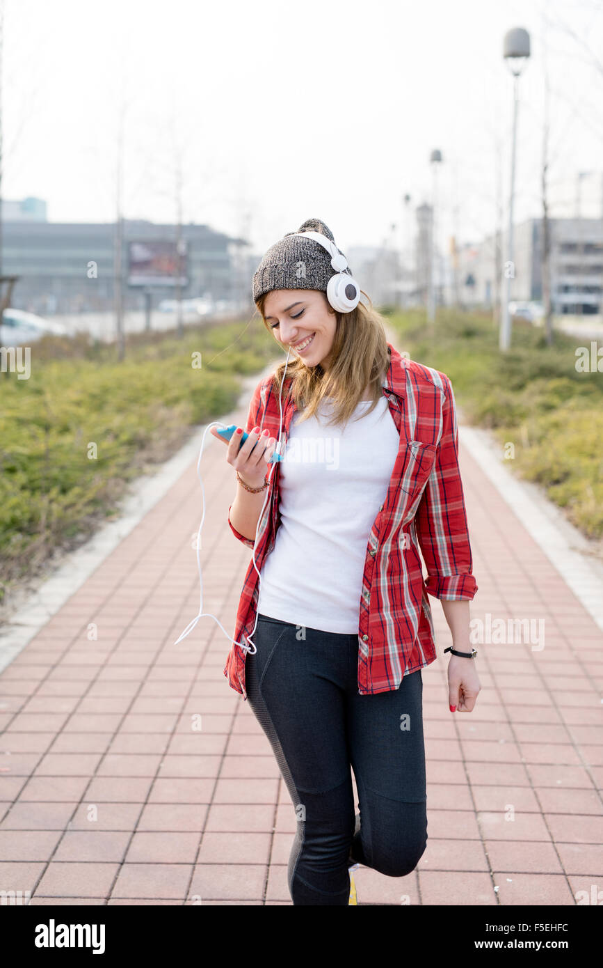 Knee figure of young straight blonde hair caucasian girl walking and dancing through the street of the city, listening - Stock Image