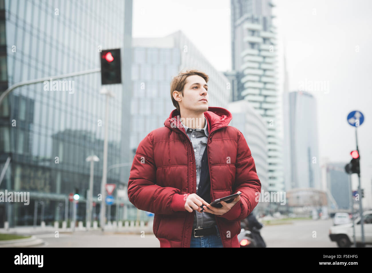 Half length of a young handsome caucasian contemporary businessman walking through the city using a tablet overlooking - Stock Image