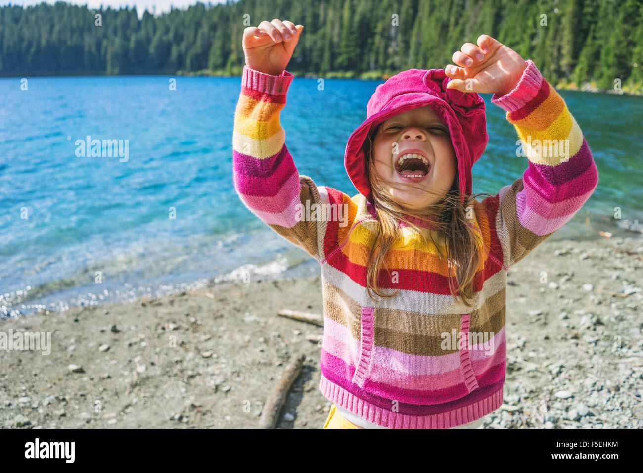 Young girl laughing with her arms in the air - Stock Image