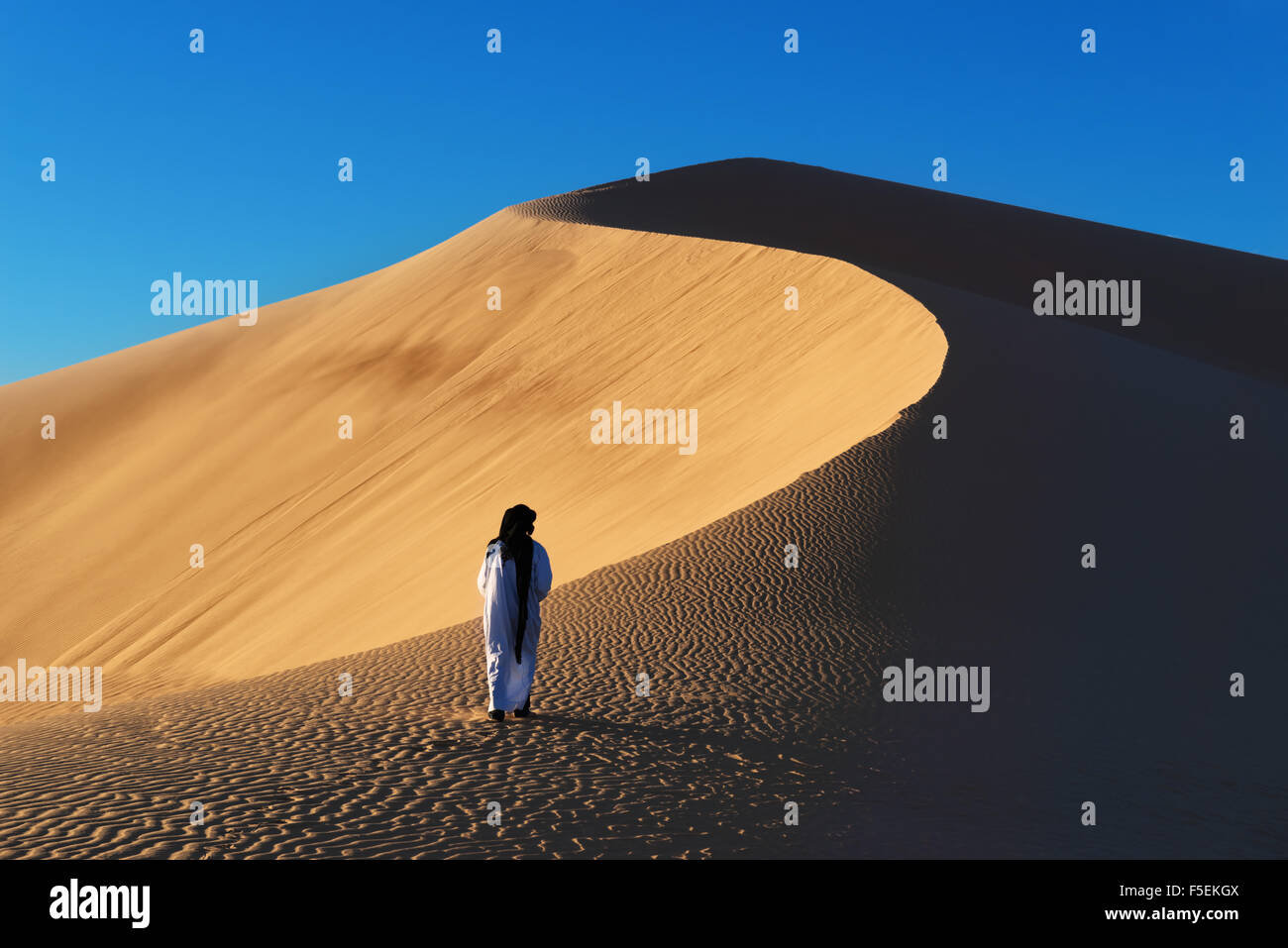 A traditional dressed Moroccan man walks up a sand dune. - Stock Image