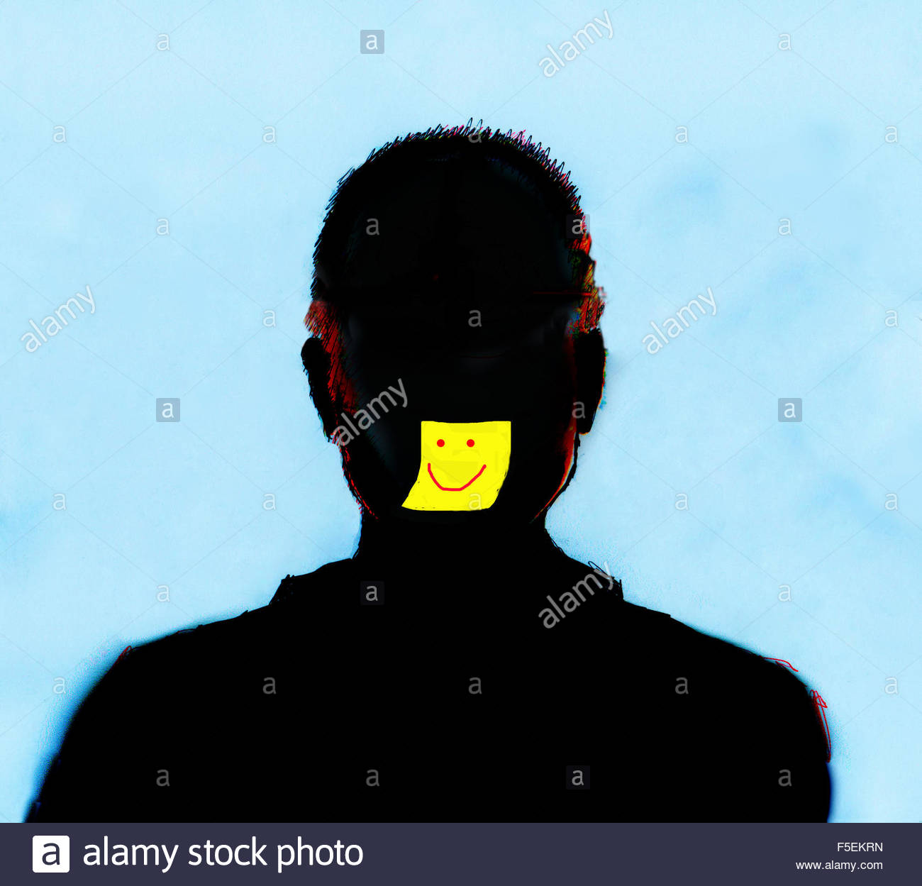 Yellow sticky note with smiley face on silhouette of man's face - Stock Image