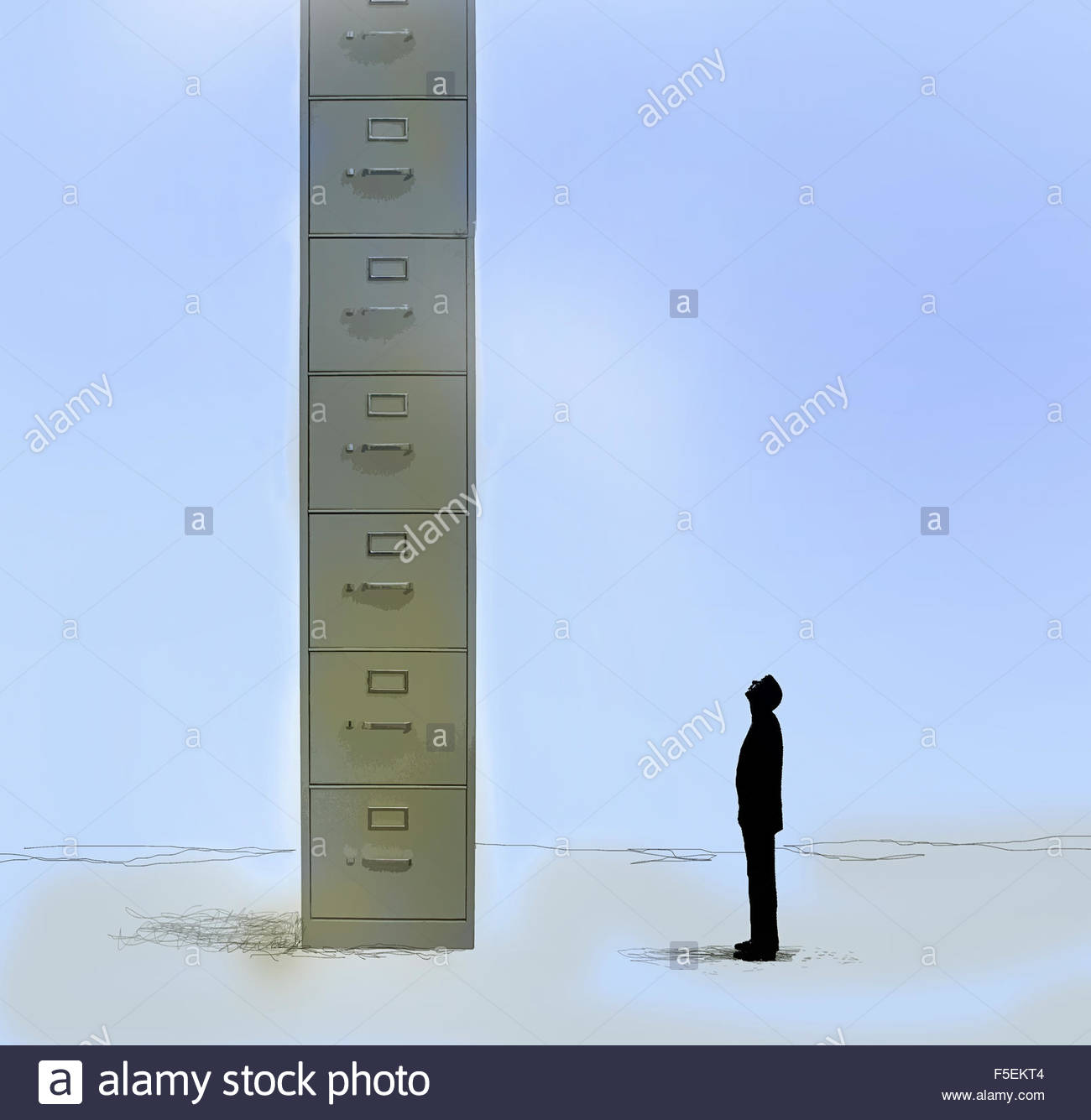 Businessman looking up at huge filing cabinet - Stock Image