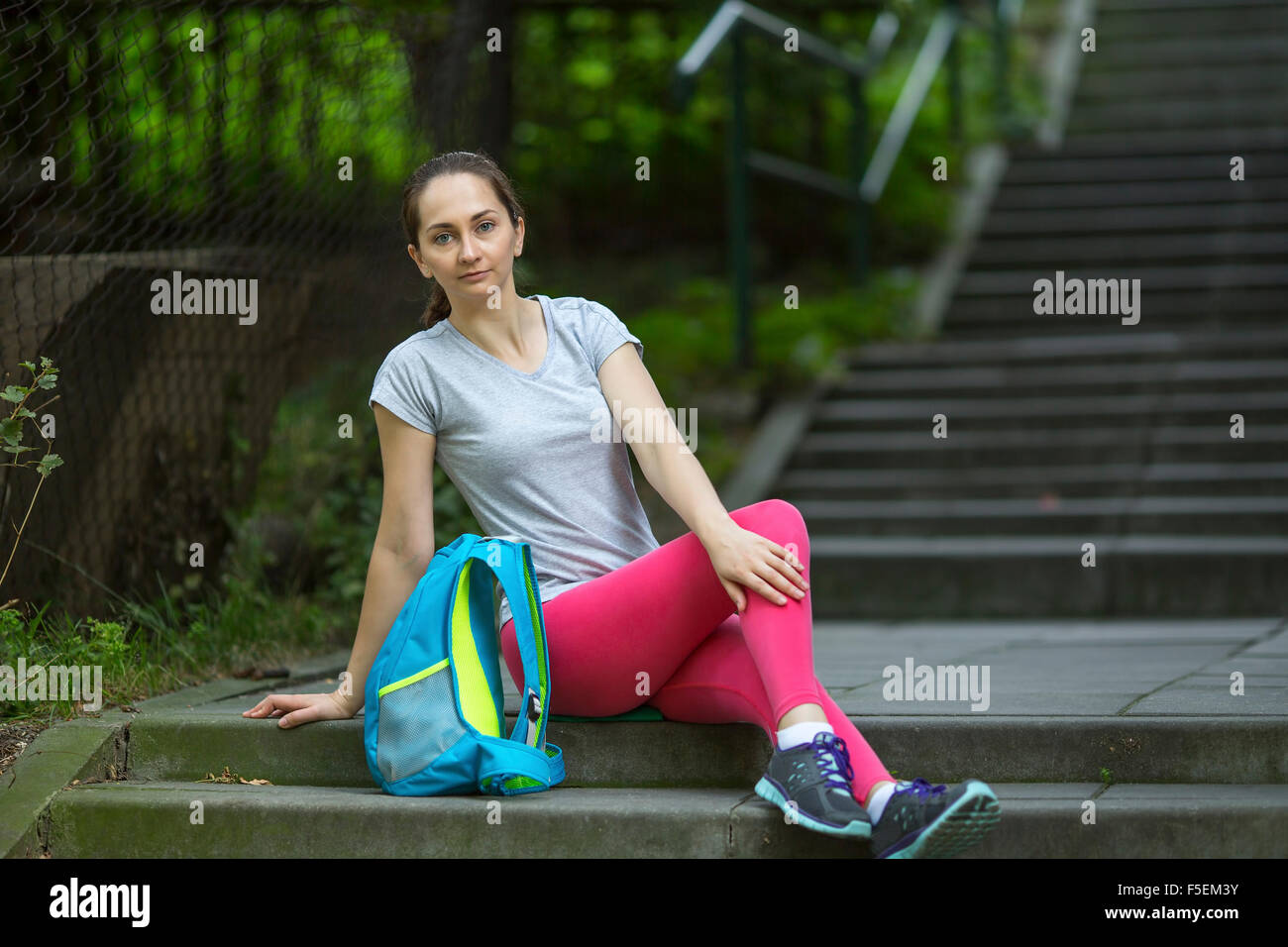 Young athlete girl sitting on the stone stairs in the Park. - Stock Image