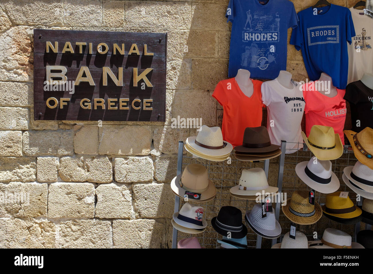 Sign for the National Bank of Greece beside a display of tourist merchandise on a wall in Rhodes Old Town, Greece. - Stock Image