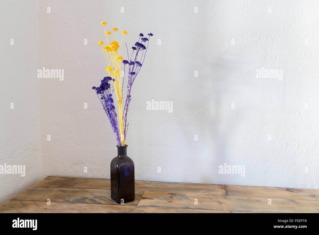 Purple and yellow dried flowers in blue bottle vase on an old wooden table Stock Photo