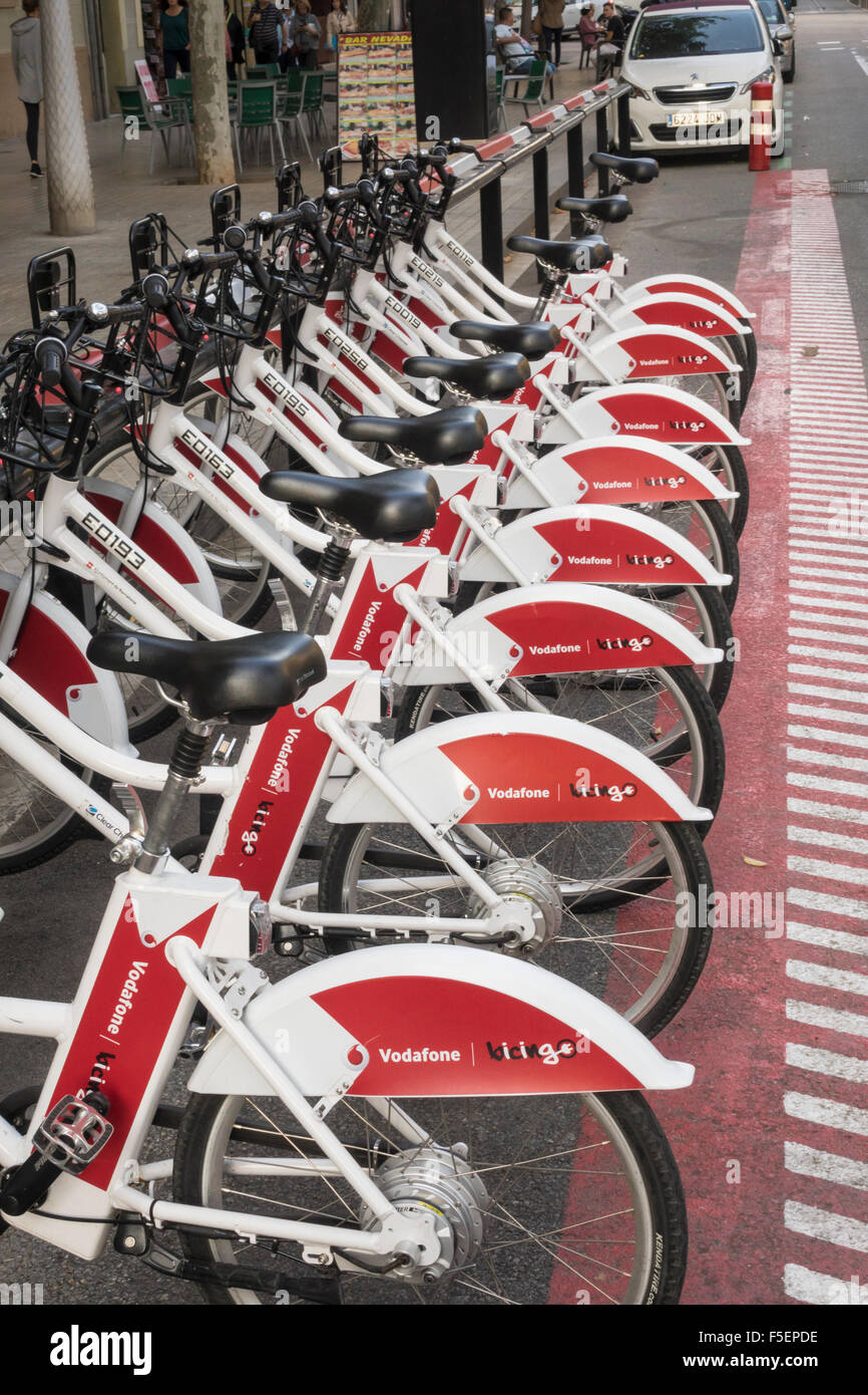 Row of Vodafone sponsored bicycles for rental in Barcelona, Spain - Stock Image