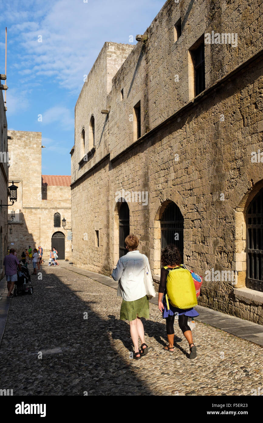 Tourists wander down the Street of the Knights, in Rhodes Old Town, Greece. - Stock Image
