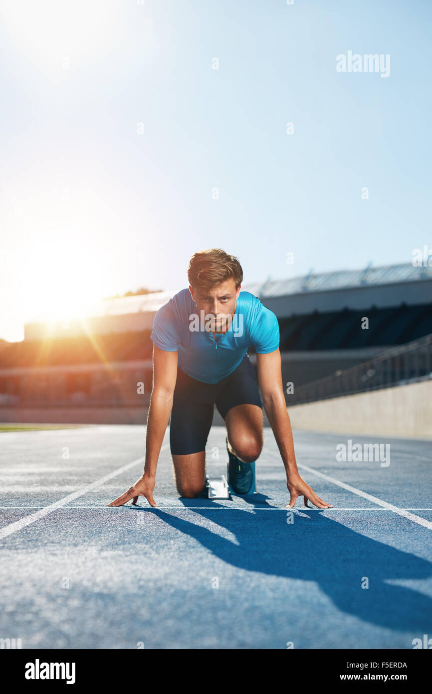 Vertical shot of young male runner taking ready to start position facing the camera. Sprinting with determination. - Stock Image