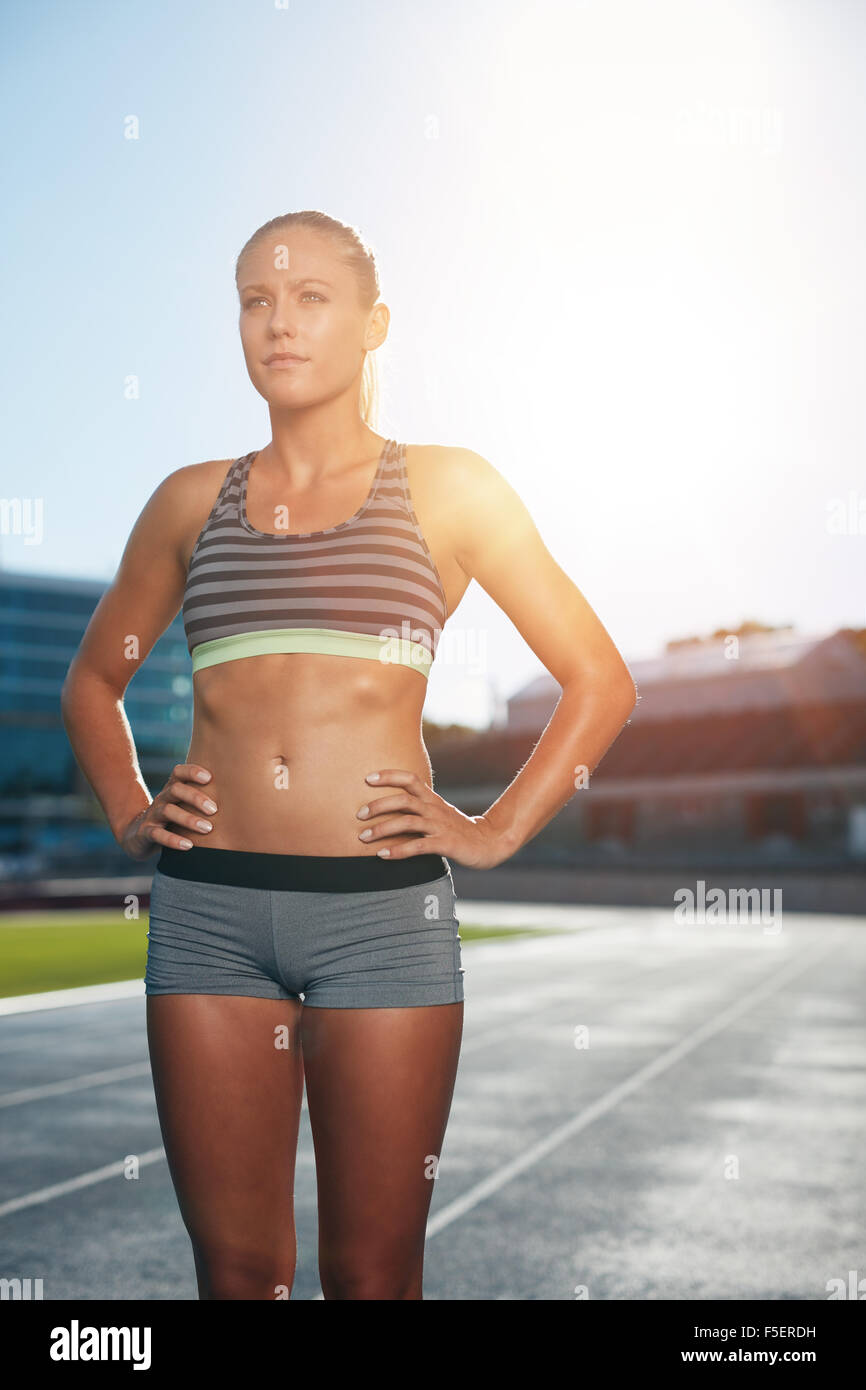 Female runner standing with her hands on hips looking away. Determined woman athlete on race track in athletics - Stock Image