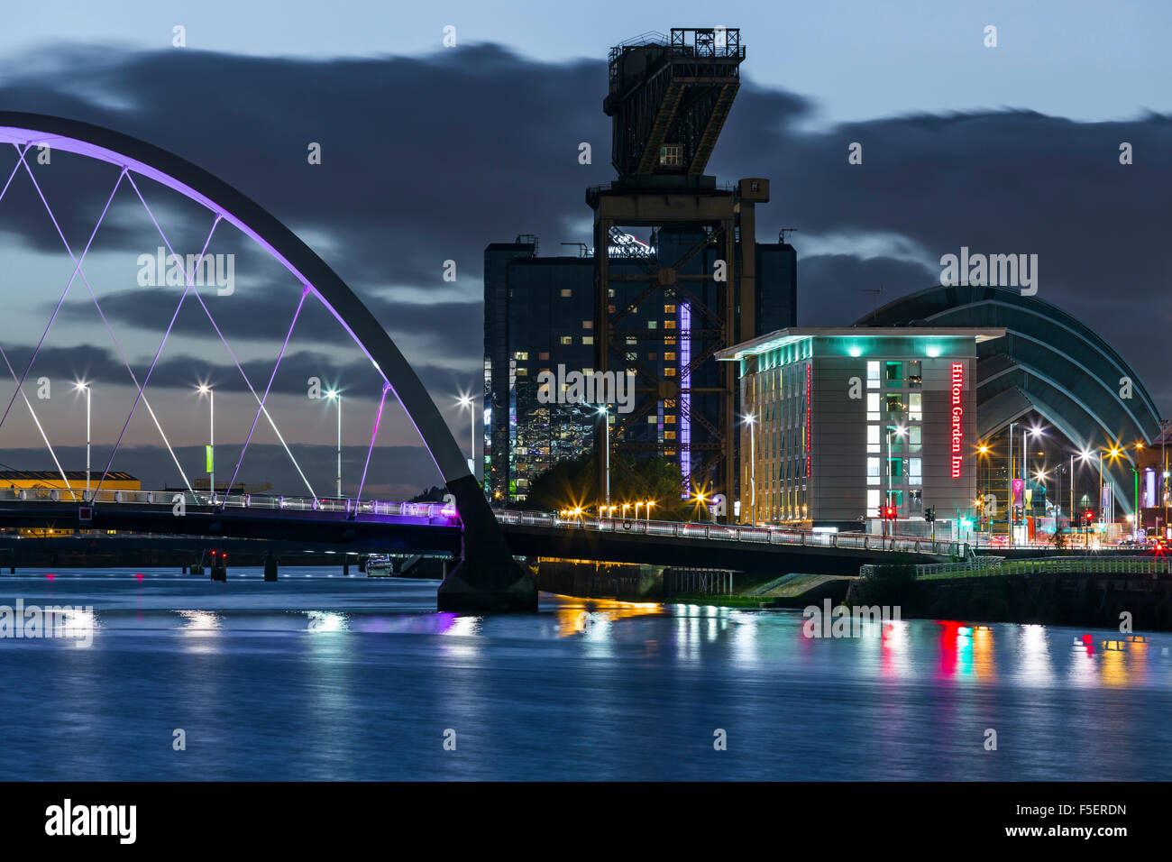 The Finnieston waterfront beside the River Clyde in Glasgow at dusk, Scotland, UK - Stock Image