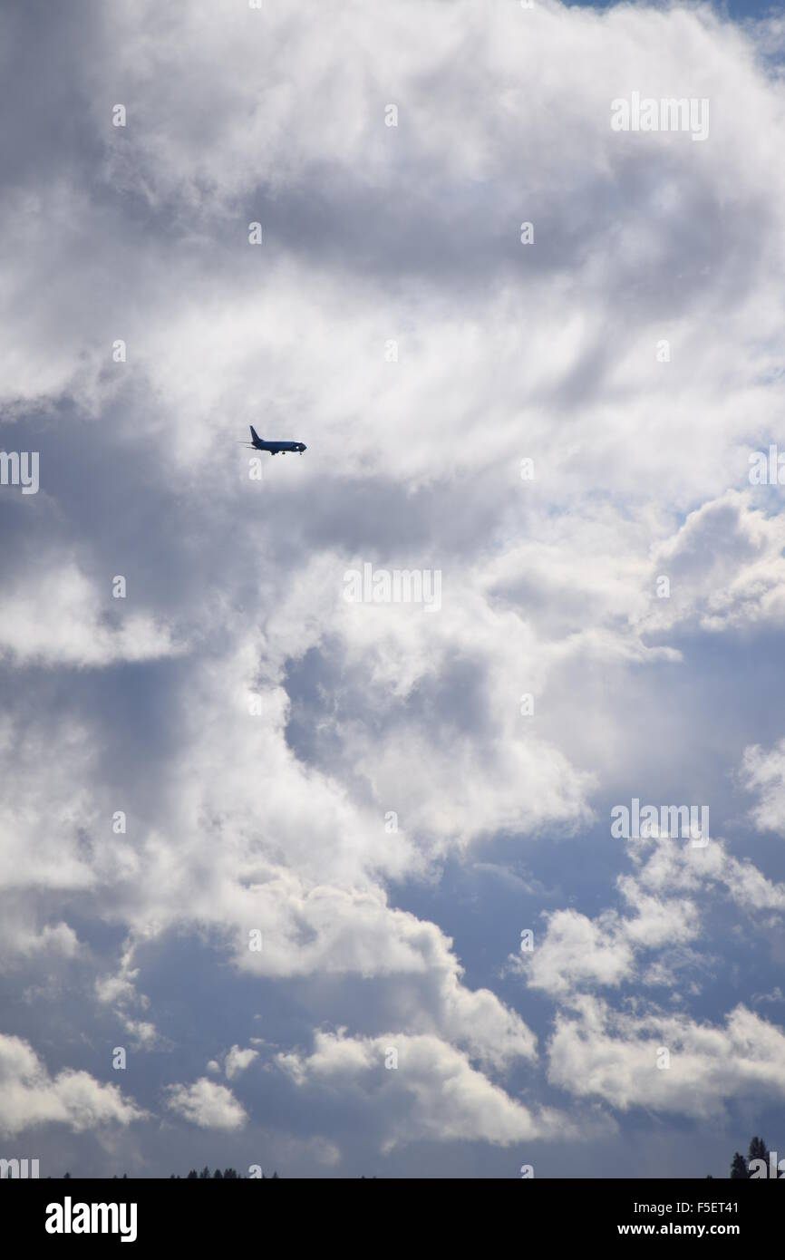 Jetliner approaching storm clouds. - Stock Image