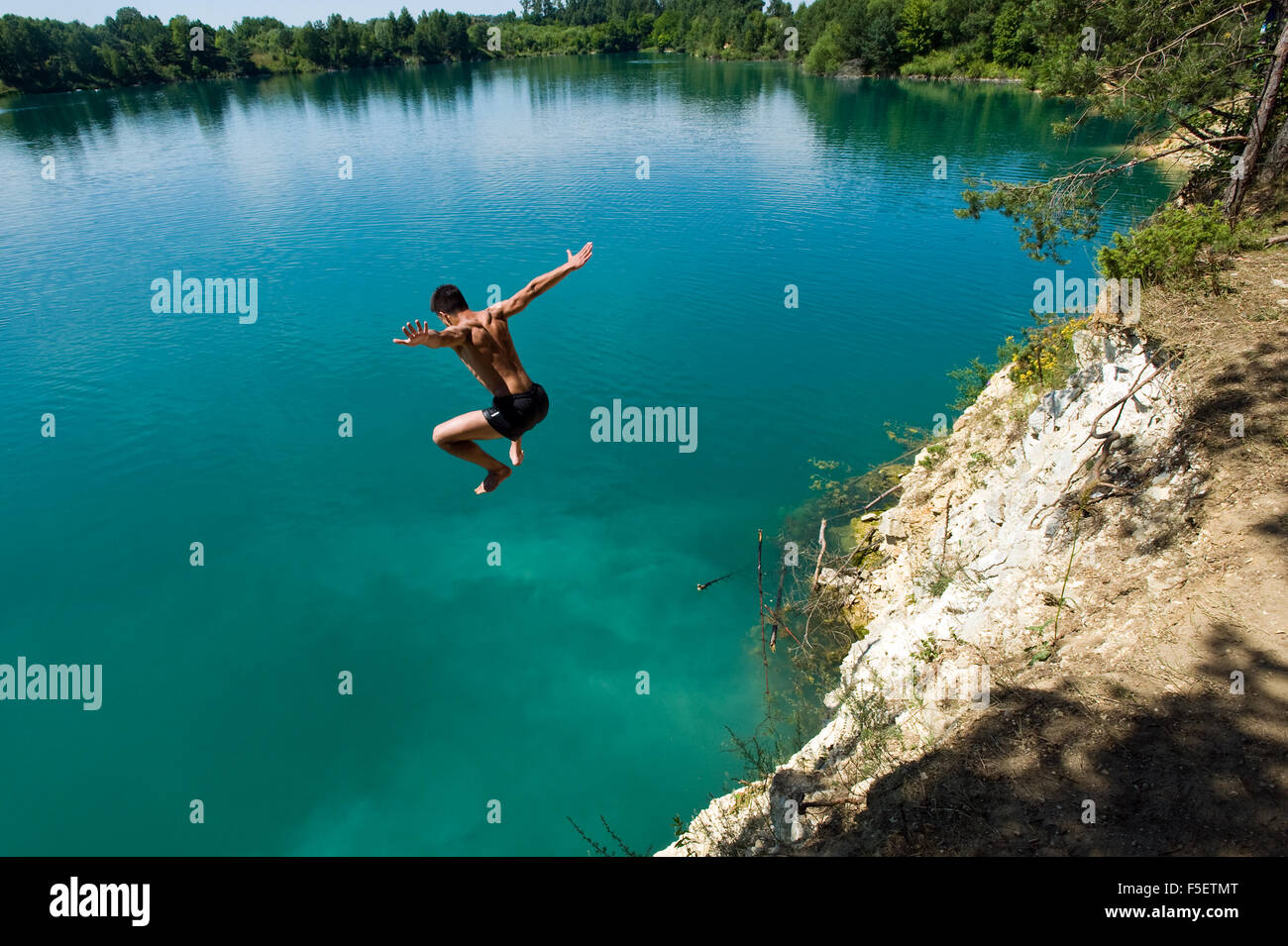 Young man jumps of the cliff to the clean, turquoise water in Sulejow. Poland. - Stock Image