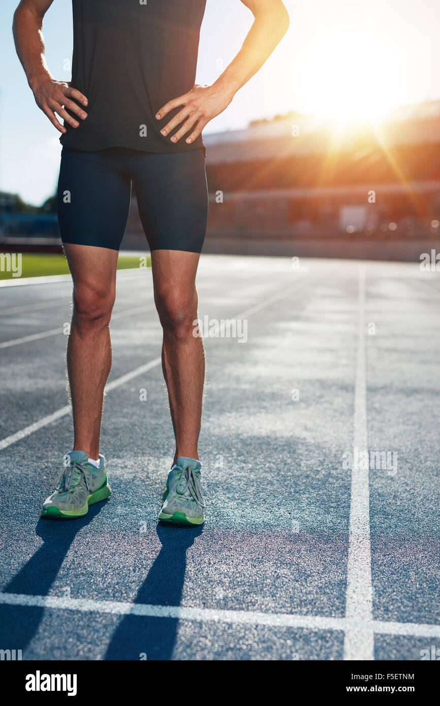 Low section shot of athlete man standing on race track with his hands on hips. Cropped shot of male runner on athletics Stock Photo