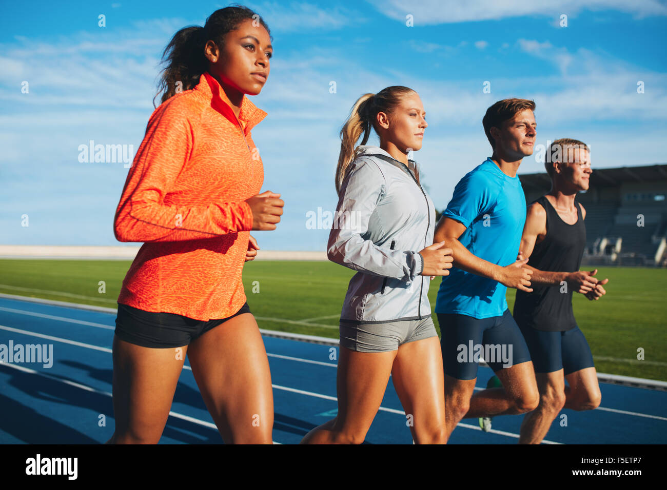 Group of diverse sports person practicing running in stadium. Male and female athletes running together on racetrack. - Stock Image