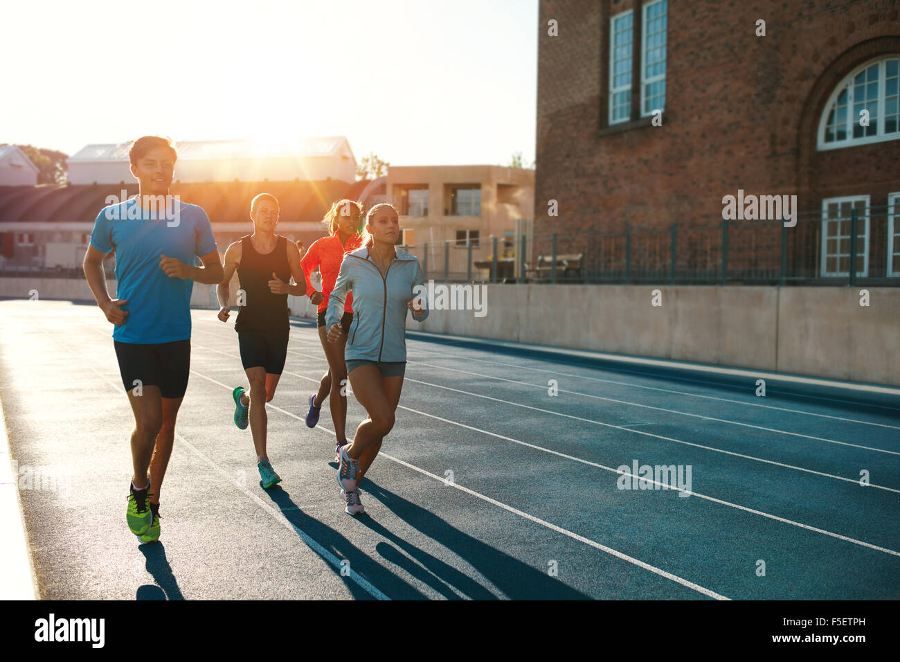 Professional runners running on a race track. Multiracial athletes practicing on race track in stadium on a bright - Stock Image