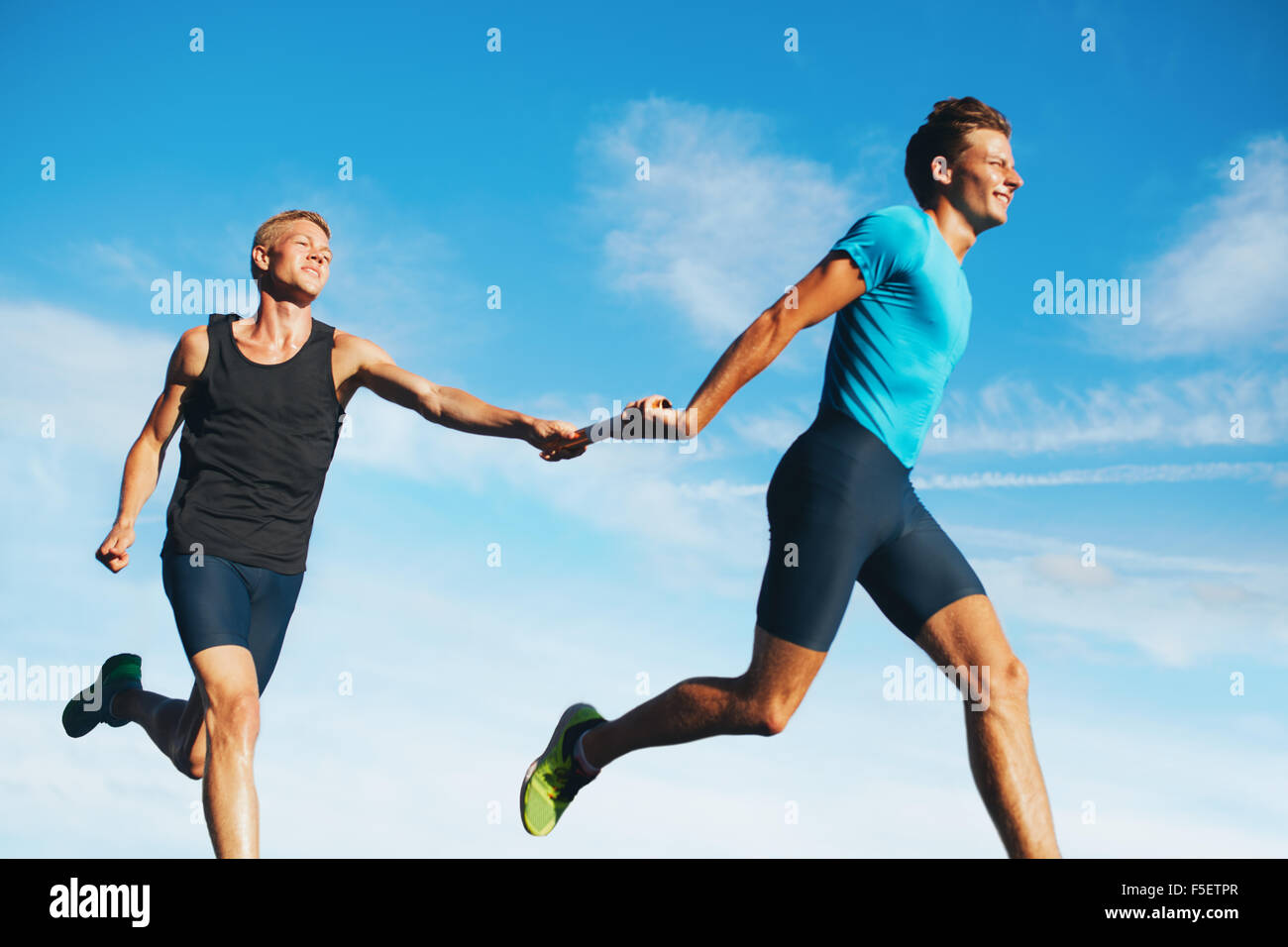 Portrait of young athletes pass the baton in a track relay against sky. Young runner practicing a relay race. - Stock Image
