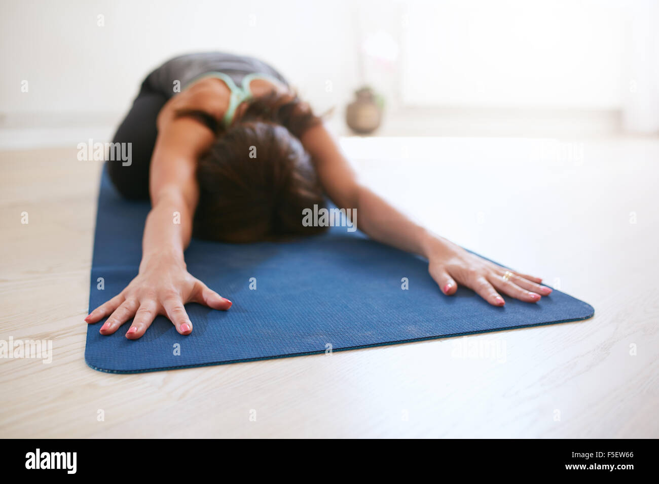 Woman doing stretching workout on fitness mat. Fit female performing yoga on exercise mat at gym. Child Pose, Balasana. Stock Photo