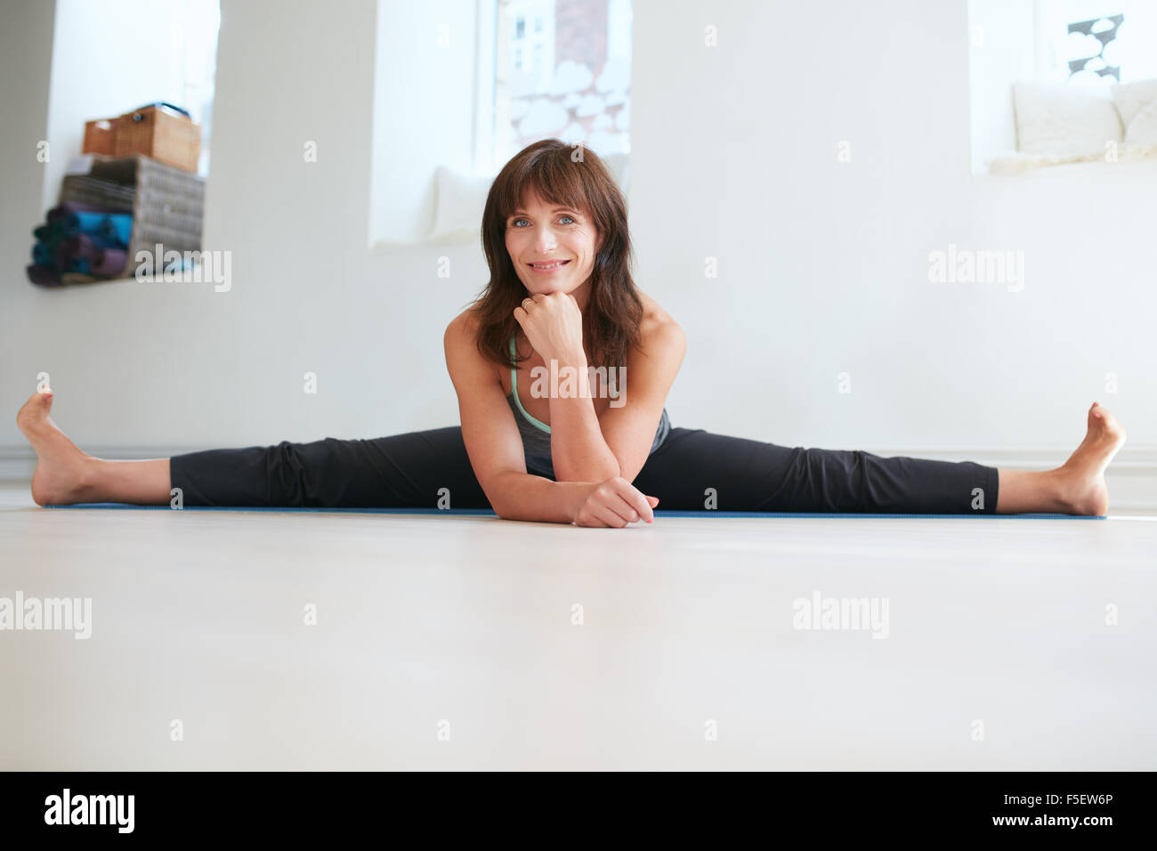 Photo of flexible woman doing the splits. Attractive female practices yoga at gym, looking at camera smiling. Upavistha - Stock Image
