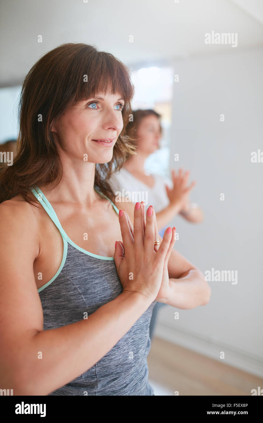 Women doing yoga exercises in class, standing in Tree Pose, Vrikshasana with namaste gesture looking way smiling. Stock Photo