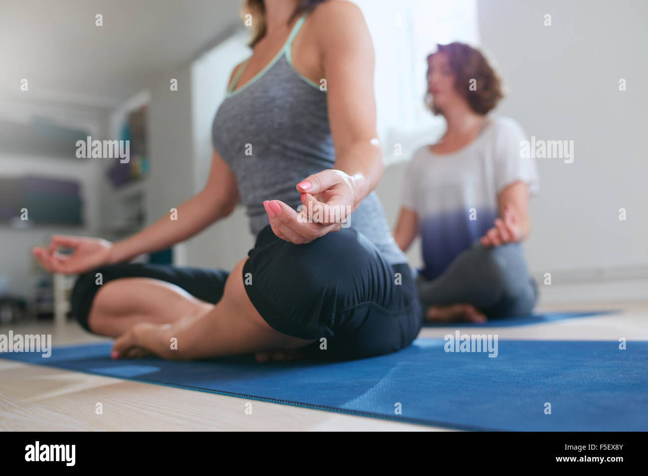 Women sitting on exercise mat with legs crossed and hands on knees. Female meditating in lotus pose at yoga class, - Stock Image