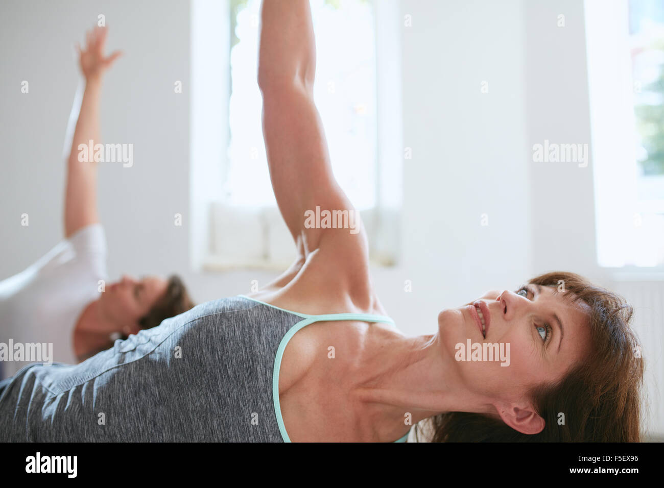 Portrait of a fit mature woman performing a yoga routine at gym. Bending over and looking away with her arms outstretched. - Stock Image