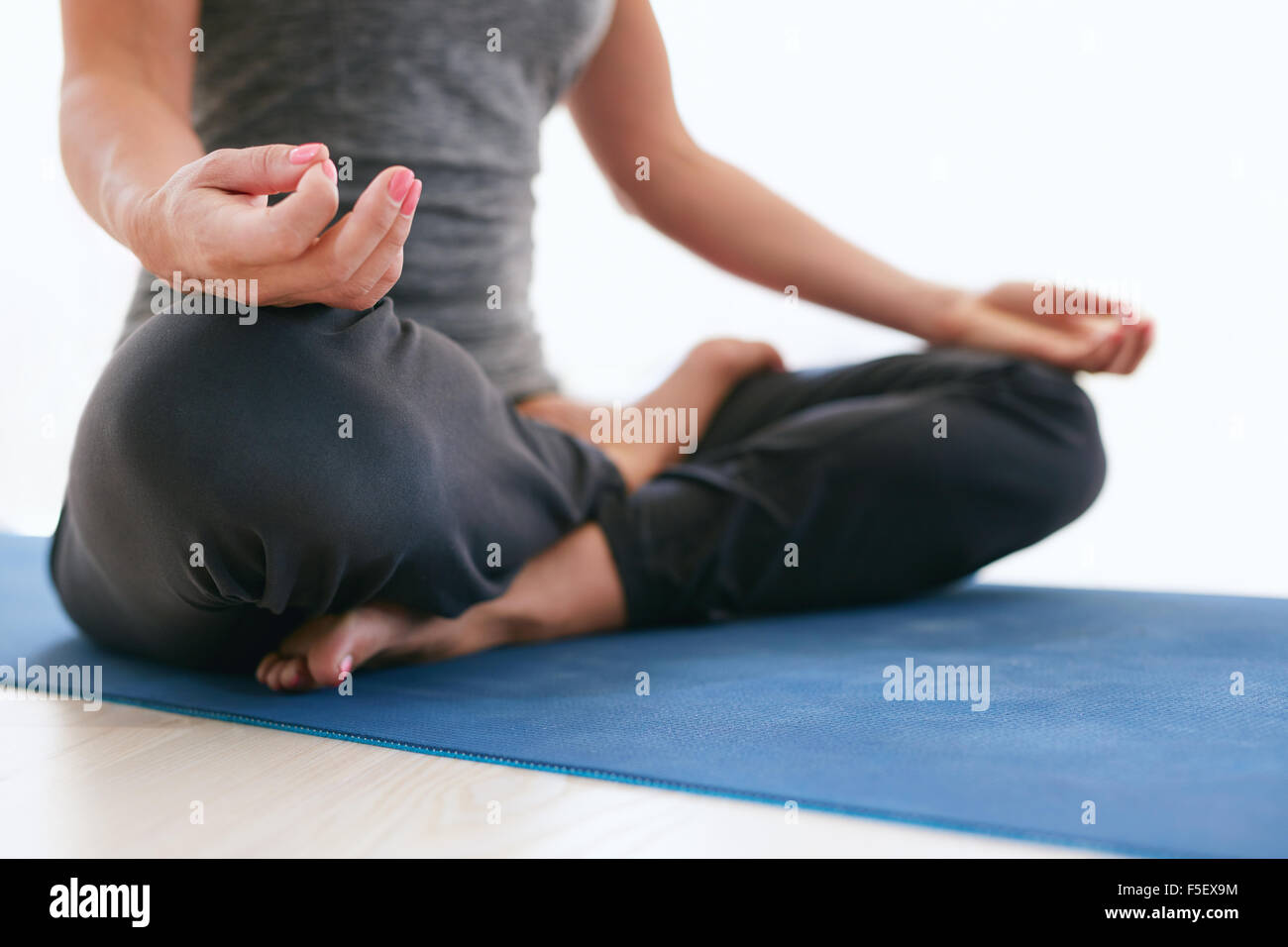 Close up of female sitting cross legged and hands on knees during meditation. Woman sitting in Lotus pose on exercise - Stock Image