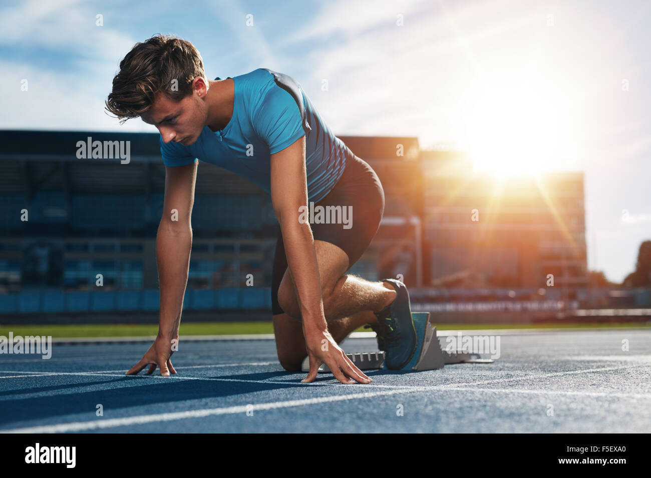Young male athlete at starting block on running track. Young man in starting position for running on sports track. - Stock Image
