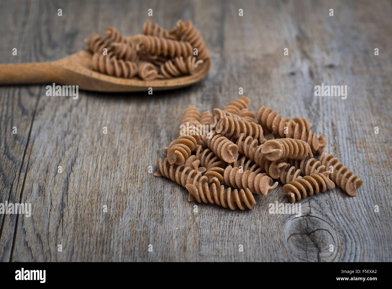 Wholegrain, spelt fusilli pasta with a wooden spoon Stock Photo