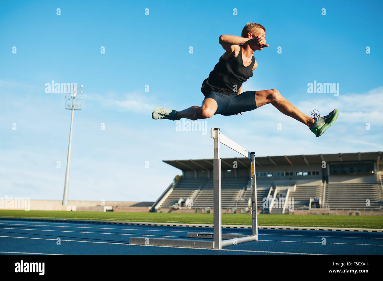 Professional male track and field athlete during obstacle race. Young athlete jumping over a hurdle during training - Stock Image