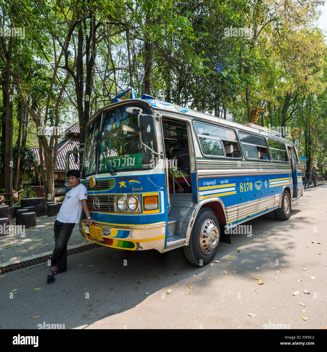 Driver leaning on his bus, Kanchanaburi Province, Central Thailand, Thailand - Stock Image