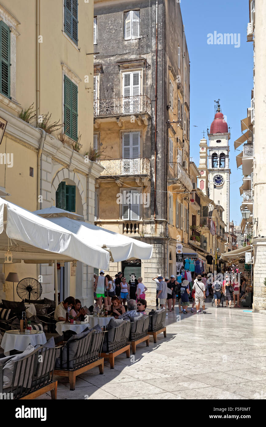 Street with restaurants and bell tower of St. Spiridon Church, Kerkyra historic centre, Corfu town, Unesco World - Stock Image