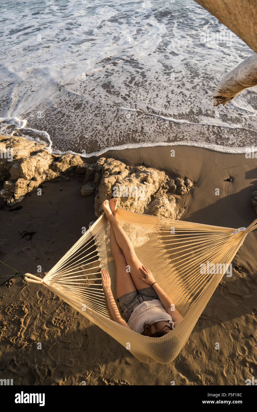 A young woman relaxing on a hammock on a beach - Stock Image