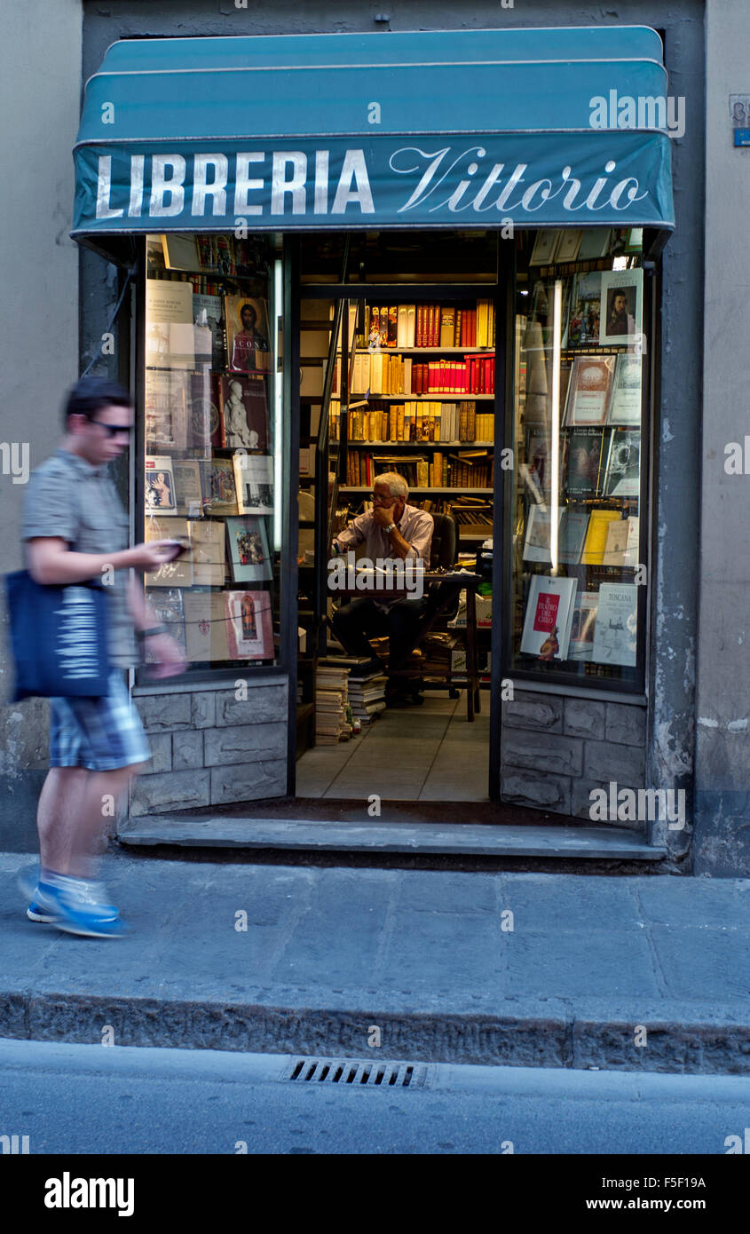 warm light coming from bookshop man walks past Liberia Vittorio Florence Italy Stock Photo