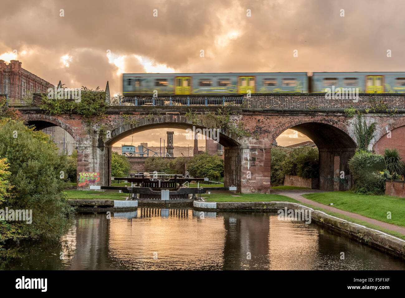 Merseyrail electric train passing over the Leeds Liverpool canal at Stanley Dock. Stock Photo