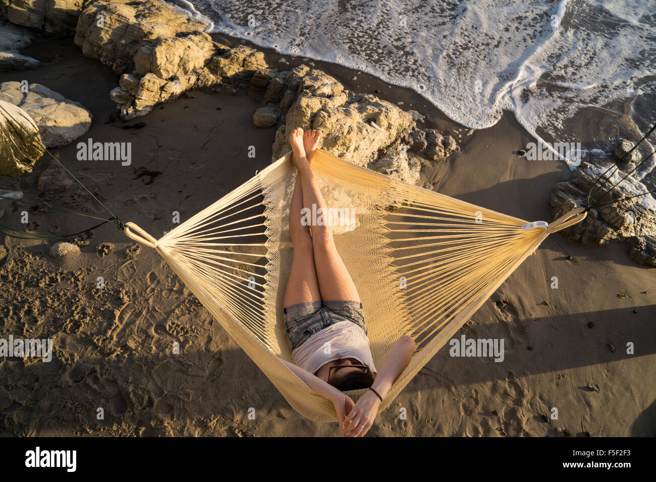 A young woman relaxing in a hammock near ocean waves - Stock Image