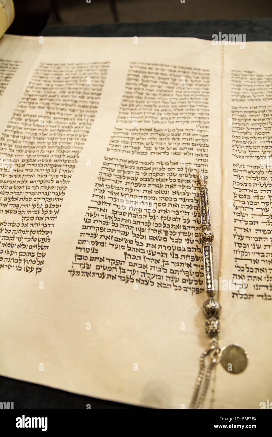 A Torah unrolled with a pointer placed on top of it - Stock Image