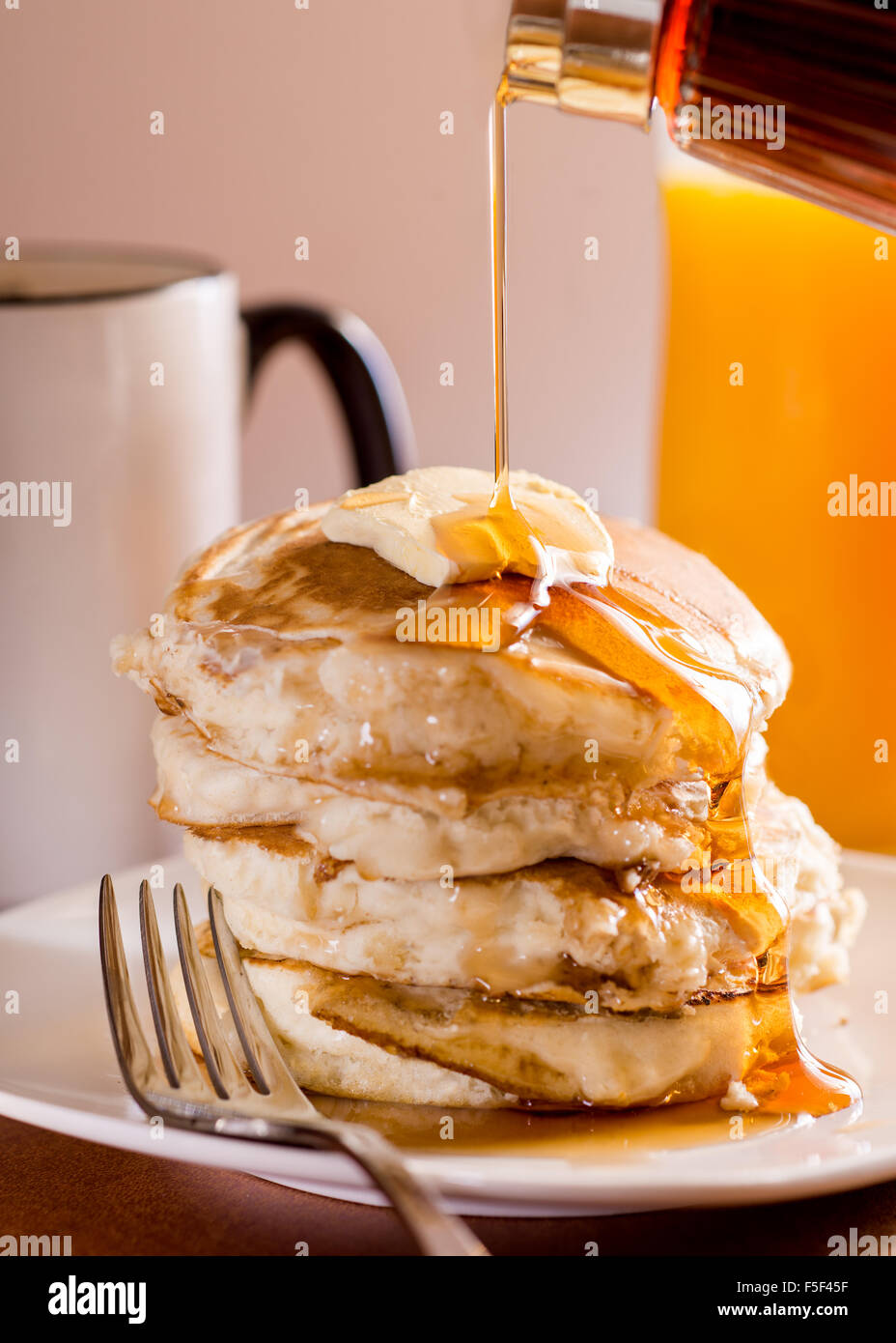 A stack of pancakes being covered in maple syrup - Stock Image