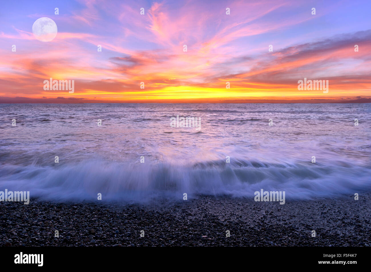 Ocean sunset moon is a color filled sky with the waves breaking on shore and the full moon rising in the background. Stock Photo