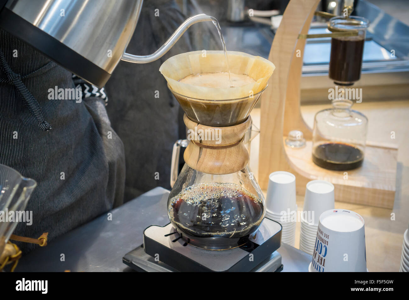 A barista prepares a pour over cup of coffee in a cafe in New York on Monday, November 2, 2015. (© Richard - Stock Image